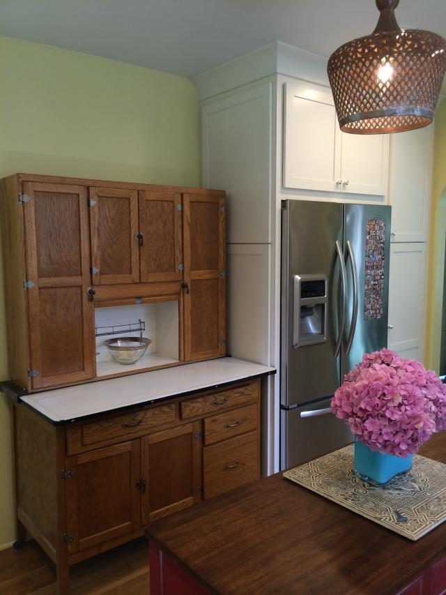 behind this hoosier cabinet is our tiny basement door
